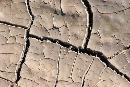 ardent: Cracked lifeless soil drying under ardent sun, macro Stock Photo
