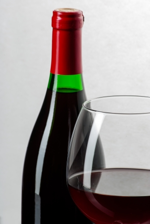 Wine bottle and a glass filled with wine on a black reflective surface photo