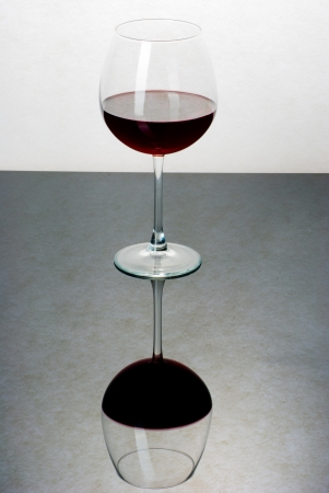 suface: A glass filled with wine on a black reflective suface