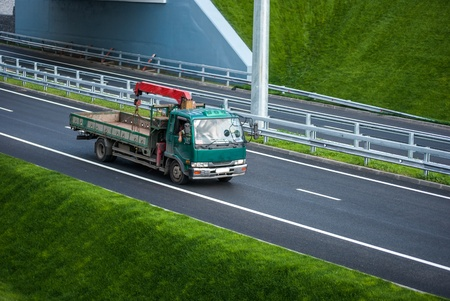 green truck with crane on the road photo