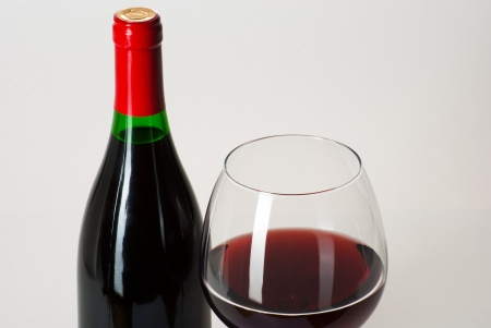 Wine bottle and a glass filled with wine isolated on white photo