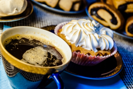 A big cupcake on a blue plate with a cup of coffee photo