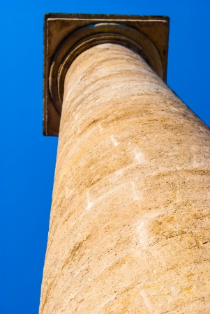 Stone column standing high against blue sky photo