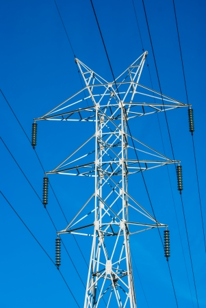 white transmission line tower against blue sky photo