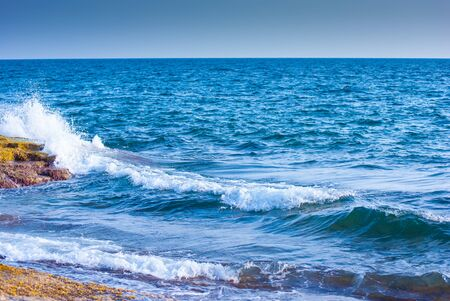 rock and splashing waves in sea photo