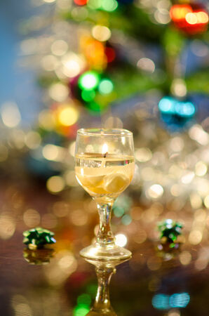 cndle in form of wine glass with seashells in front of Christmas tree photo