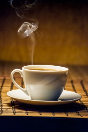 white cup of coffee on wooden mat Stock Photo