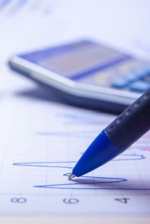 pen and calculator on graph paper with diagram Stock Photo