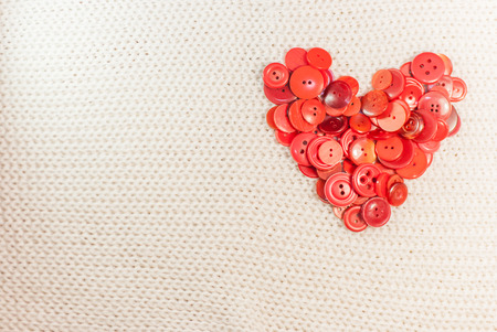 heart of red buttons on woven fabric photo