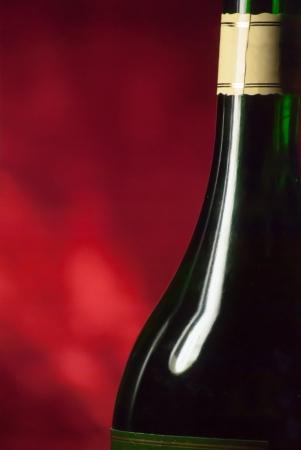 unopened: Unopened wine bottle on red