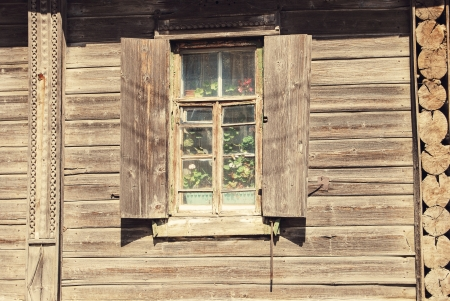 open window with flowers in wooden house, russian countryside photo