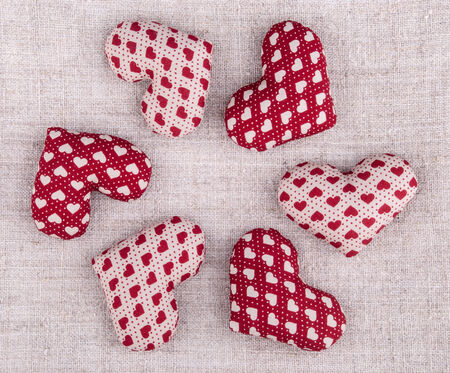 six red hearts on rough textile arranged in circle