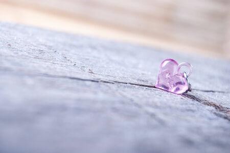 plastic heart: pink plastic heart on wood Stock Photo