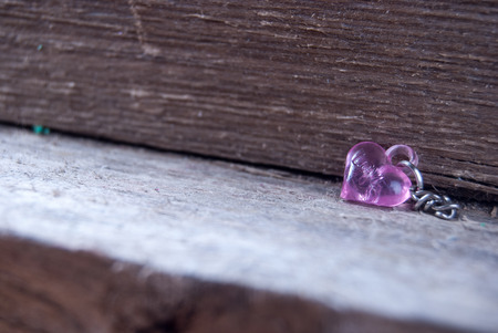 plastic heart: pink plastic heart on wood Stock Photo