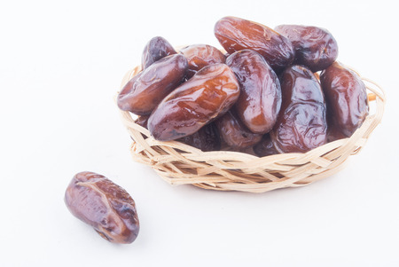 dried fruits from date palm in basket isolated on white Stock Photo