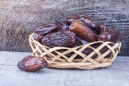 dried fruits from date palm in basket against wood photo
