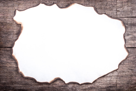 burnt paper on wood, can be used as a background or a frame for text photo