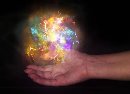 Bright light ball over human hand isolated on black background photo