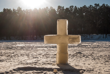 ice christian cross on frozen lake photo