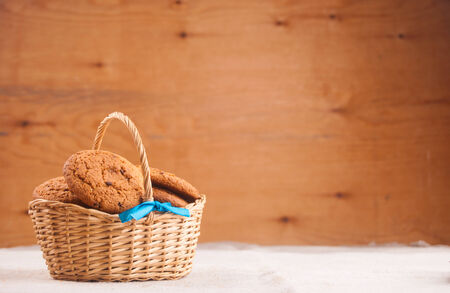 oatmeal cookies: Oats cookies in basket against wood Stock Photo