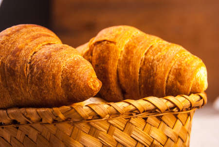 Croissants in a basket on wooden table covered with rough fabric photo
