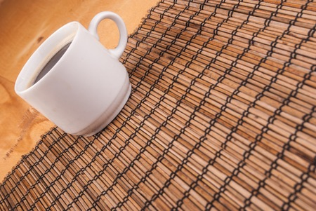 espresso coffee in a white china cup over wooden mat photo