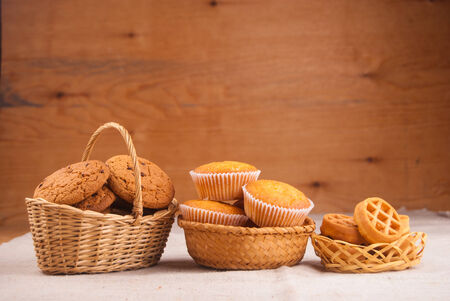 Oats cookies, cupcakes, and waffles in in basket against wood