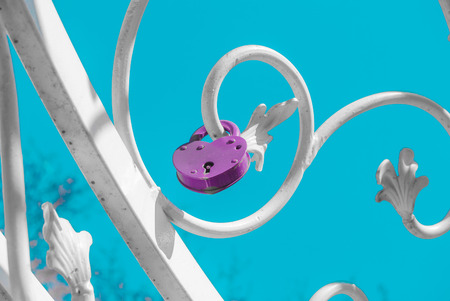 white forged plant ornament with purple padlock against blue sky photo