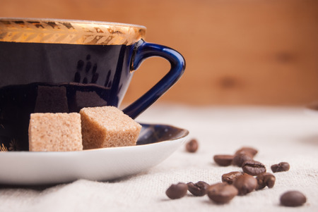 Blue china cup with brown sugar and coffee beans photo