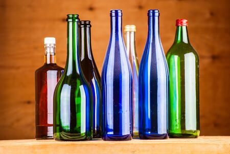alcohol bottles: colorful wine bottles on a wooden background Stock Photo