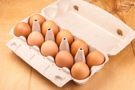 ten chicken eggs in the container on wood, background with space for text
