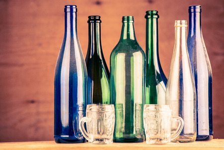 colorful wine bottles on a wooden background photo