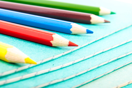 Stack of notebooks and colorful pencils isolated on white photo