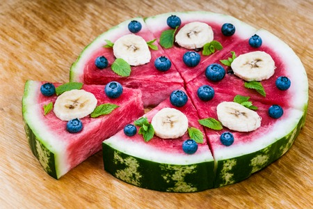 sliced watermelon: Sliced juicy watermelon pizza on wood, closeup view from above. Ingredients are watermelon, blueberries, banana, mint, and coconut shavings.