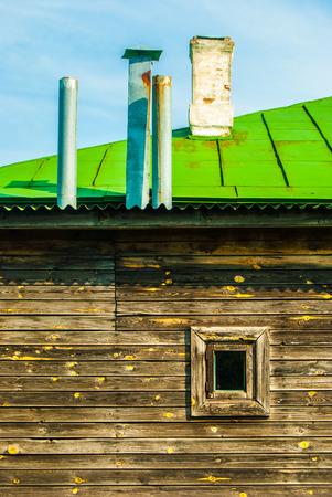 Old wooden house with tiny window and several chimneys photo