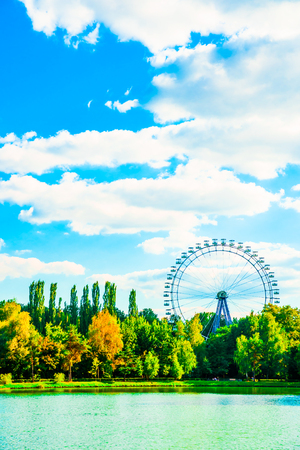 Big ferris wheel in city park. Beautiful landscape with lake, trees blue sky, and clouds photo