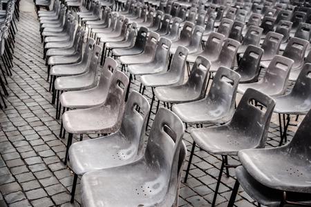 public sector: Rows of empty plastic seats on stone pavement, outdoor setting