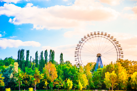 Big ferris wheel in city park landscape with lake, trees blue sky, and clouds photo