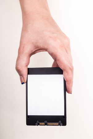 solid state drive: Female hand showing a Solid State Drive on white