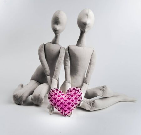 textile image: Two handmade textile dolls holding red heart. Image of love, affection.