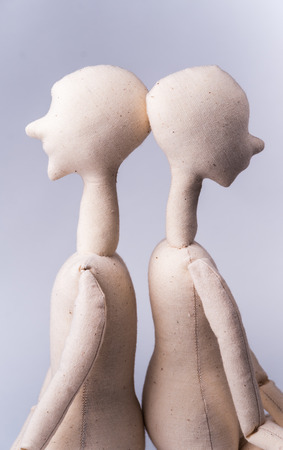 textile image: Two handmade textile dolls sitting together. Image of love, affection.