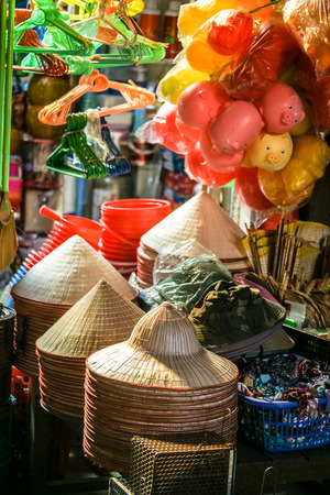 conical hat: Market in Vietnam with flowers, piggy banks, and traditional conical hats