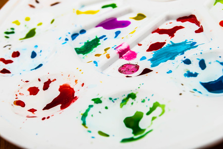 White plastic art palette with random watercolor paint blobs on wood photo