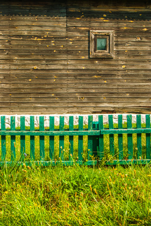 Old wooden house with tiny window standing behind green fence on grass photo