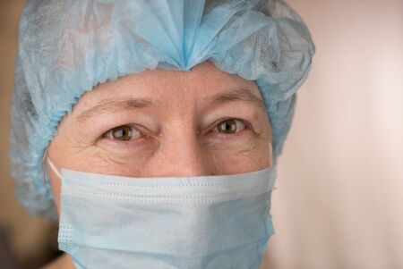 Female doctor wearing medical mask and surgical cap looking at patient and smiling photo