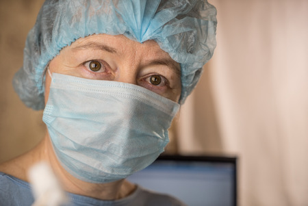Female doctor wearing medical mask and surgical cap looking seriously and worried at patient with computer in background Stock Photo