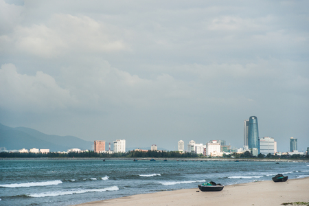 nang: Traditional fishing boats on the beach of Da Nang city, the cityscape and Son Tra peninsula are visible in distance. Vietnam.