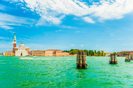 buoys: View of San Giorgio Island in Venice with wooden buoys in Giudecca Canal. The  San Giorgio church and monastery are seen on the island. Stock Photo
