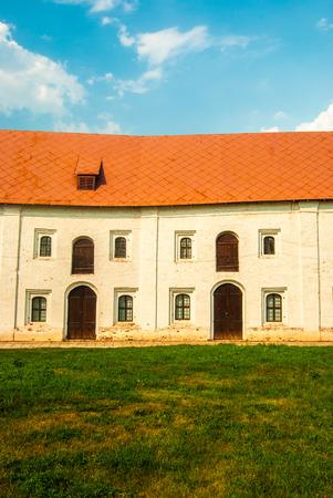 puertas de hierro: Casa vieja del ladrillo con puertas de madera y ventanas con rejas de hierro. El techo de metal se pinta de rojo. Foto de archivo