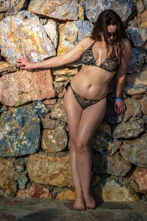 ligh: Young caucasian woman posing against stone wall in gentle ligh of summer evening